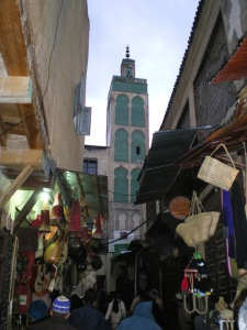 A medersa towering over the souk's alleyway deep within the Fez medina